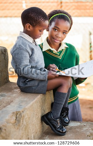 A sister are helping her little  brother with his home work. - stock photo