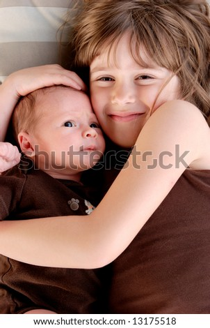 A sister giving her baby brother hugs - stock photo