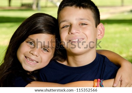 a sister giving her brother a big hub while they smile in the park. - stock photo