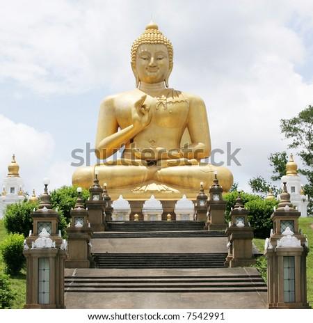 A sitting Buddha statue against a blue sky. - stock photo