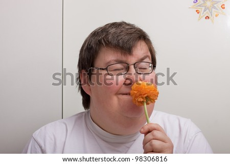 a sitting mentally disabled woman is smelling a flower - stock photo