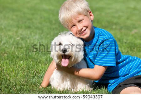 A sitting on the grass smiling boy is hugging his pet