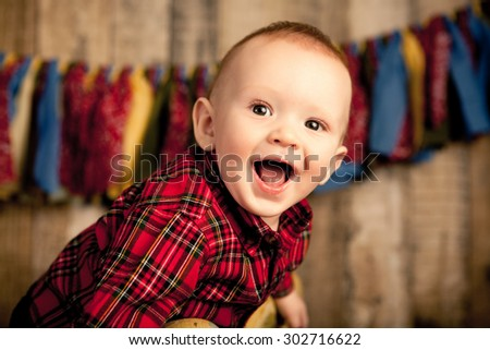 A six month old baby boy smiling on a wood background. - stock photo