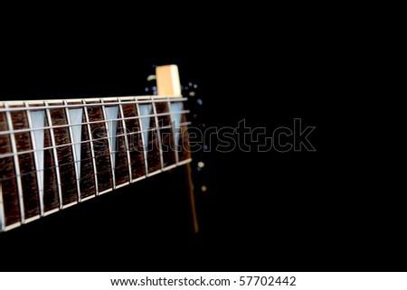 A six string electric guitar neck isolated on a black background