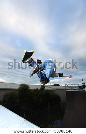 A skateboarder gets air off the top of a skate ramp. - stock photo