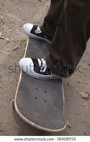 A skateboarder standing on his skate. Close-up of feet. - stock photo