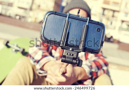 a skater taking a self-portrait with a selfie stick - stock photo