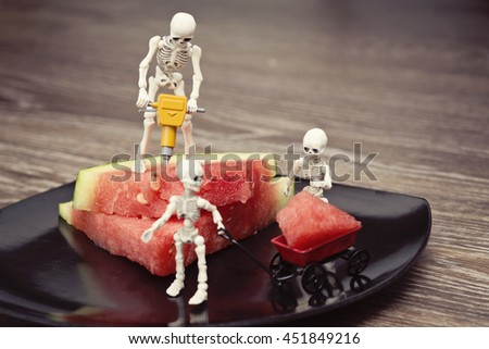 A skeleton cutting watermelon with jackhammer and skeleton kid load it n toy wagon - stock photo
