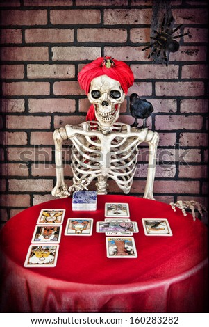 A skeleton doing a Tarot card reading. - stock photo