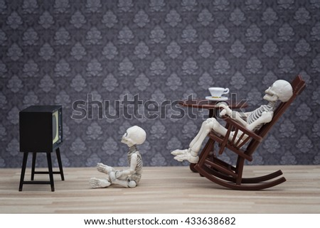 A skeleton sitting in a rocking chair while little skeleton sitting on the floor watching TV