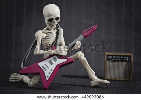 A Skeleton taping his electric guitar - stock photo