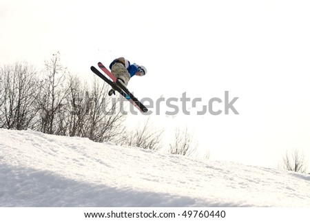 A skier catching some major air after launching off of a jump. - stock photo