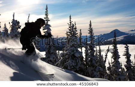 A skier glides through fresh powder on a sunny day. - stock photo