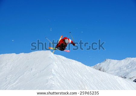 a skier with crossed ski landing on a jump ramp with crossed skis and with a horizontal body position and flashes of snow in the air