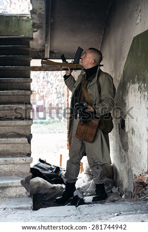 A skinhead hitman looks up the stairs - stock photo
