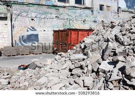 A skip full of rubble outside a construction site - stock photo