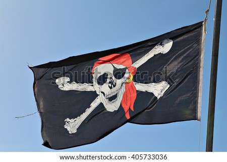 A skull and cross bones pirate flag waving in the wind. - stock photo