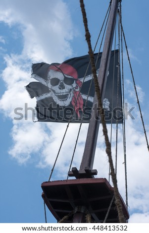 A skull and cross bones pirate flag waving in the wind - stock photo