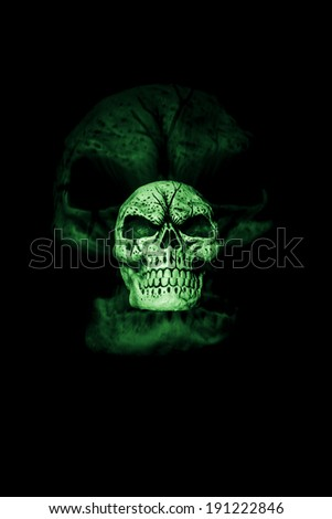 A skull is isolated on a black background with a larger skull ghost image behind it. - stock photo