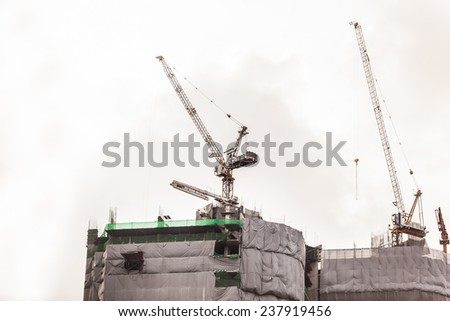 a skyscraper under construction or renovation with cranes and scaffolding - stock photo
