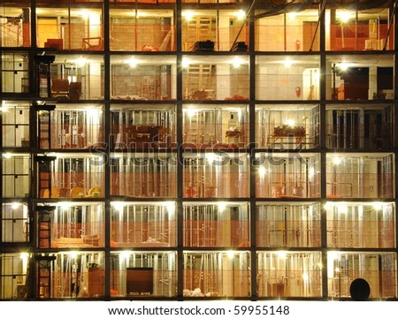 A skyscraper under construction with exposed floors at night. - stock photo