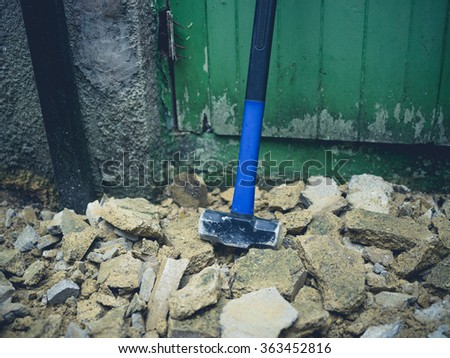 A sledge hammer and rubble outside - stock photo