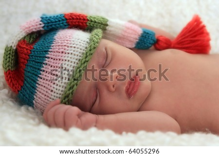 A sleeping baby girl wearing a striped hat - stock photo