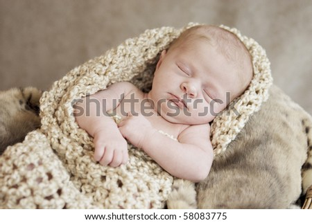 A sleeping newborn baby girl in a warm crocheted cocoon, selective focus with focus on face - stock photo