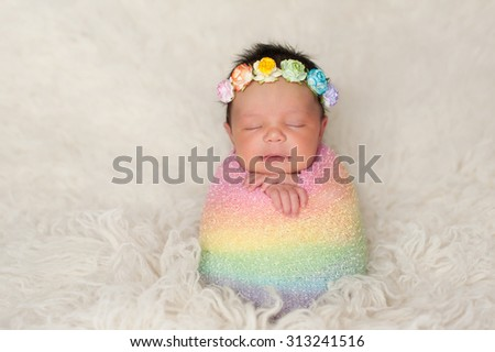 A sleeping nine day old newborn baby girl bundled up in a rainbow colored swaddle. She is propped up on a cream colored flokati (sheepskin) rug and wearing a crown made of roses. - stock photo