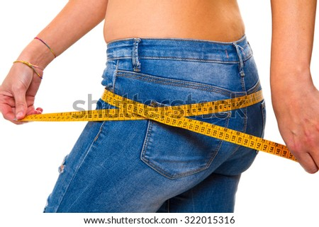 a slender young woman in jeans with a tape measure after a successful diet - stock photo