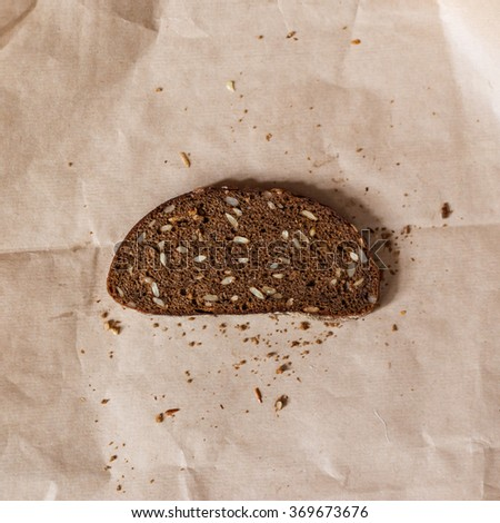 a slice of black bread with sunflower seeds - stock photo