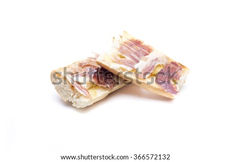 a slice of bread with oil and ham, typical Spanish breakfast - stock photo