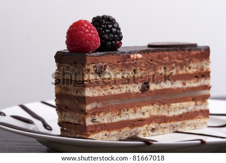 A slice of chocolate cake topped with a raspberry and blackberry on a white plate. - stock photo