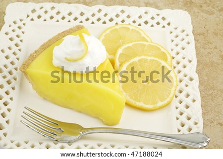 A slice of cool and refreshing lemon icebox pie topped with whipped cream and garnished with sliced lemons, horizontal with copy space