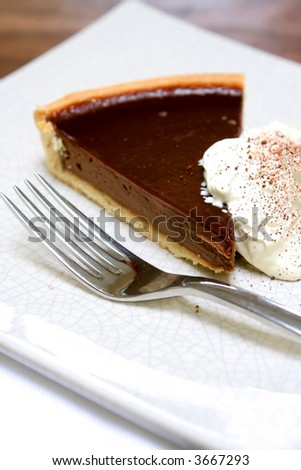 A slice of delicious chocolate tart gateaux served with fresh whipped cream with sprinkling of chocolatedust. - stock photo
