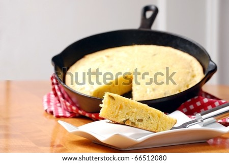 A Slice of Freshly Baked Cornbread on a White Plate with the Cast Iron Pan in the background - stock photo