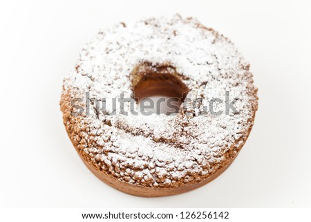 A slice of freshly baked ring cake with icing sugar