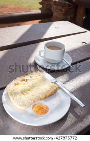 A slice of freshly baked white bread lies on a plate on an outside table, already spread with butter, with sam marmalade next to it, and a cup of coffee behind. - stock photo
