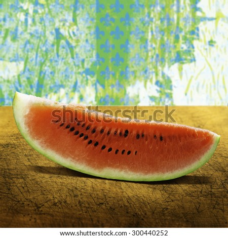 A slice of juicy watermelon on a wooden board and green background - stock photo