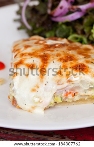 A slice of leek and goats cheese quiche on a plate with crispy leaf salad and tomato - stock photo