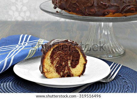 A slice of marbled chocolate and vanilla cake with chocolate fronting in front of a cake stand with whole cake. - stock photo
