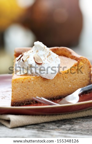 A slice of Pumpkin Cheesecake Pie with homemade whipped cream, alomonds and pumpkin spice. Extreme shallow depth of field. - stock photo