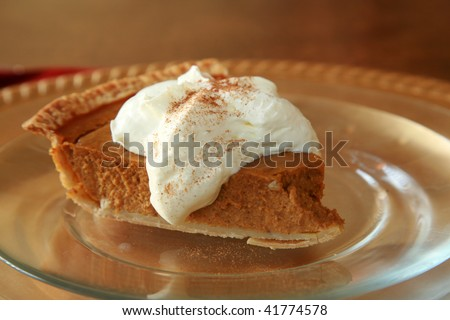 a slice of pumpkin pie on a plate with whip cream