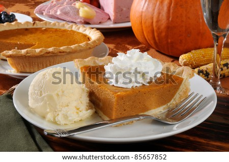 A slice of pumpkin pie with ice cream and a Thanksgiving dinner in the background - stock photo