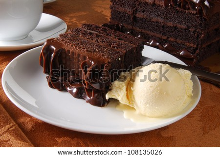 A slice of rich chocolate cake with ice cream and coffee - stock photo