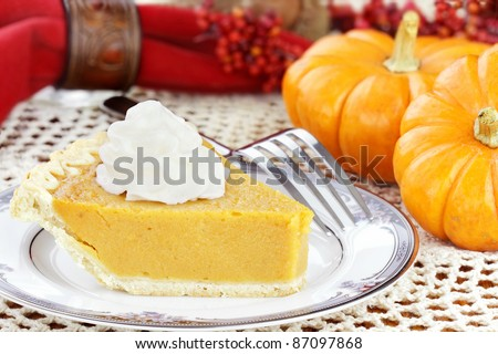 A slice of sweet potato or pumpkin pie with whipped cream. Selective focus on pie.