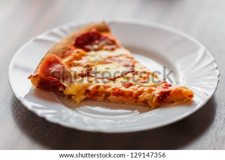 A slice of tasty pizza on a plate - stock photo
