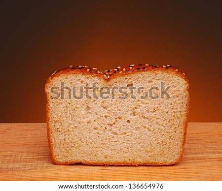A slice of whole grain bread on a wood table and a war light to dark background.