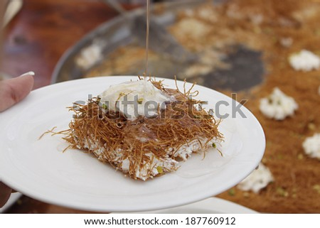 A slice piece of Esmalliyeh, a traditional Arabic sweet pastry, in a white platter with syrup drizzling on. - stock photo