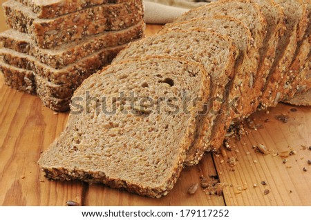 A sliced loaf of sprouted grain and seed bread on a cutting board - stock photo